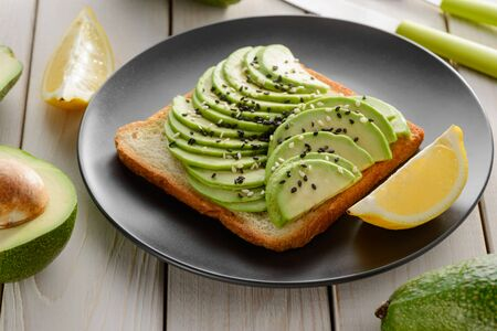 Perfect avocado toast with sesame seeds and lemon on a black plate. Healthy food and vegetarian diet.