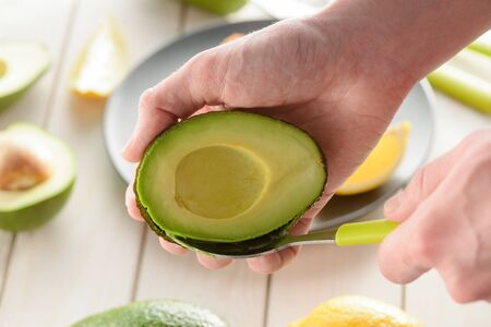 Man preparing avocado, scooping its flesh out with a spoon. Simple recipe. Healthy cooking concept.