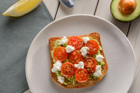 Toast with mashed avocado, sliced tomato and ricotta