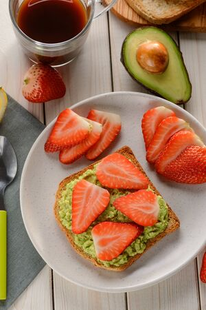 Avocado toast with strawberry slices. Delicious snack for breakfast or lunch. Quick and simple vegan recipe. Reklamní fotografie