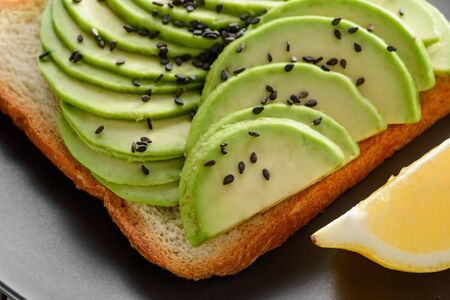 Toast with avocado slices. Closeup on tasty breakfast snack