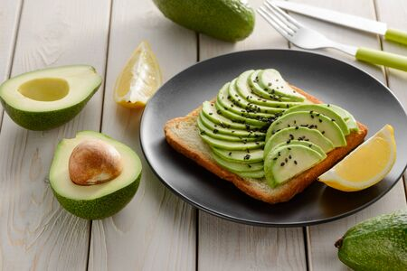 Toast with sliced avocado and lemon juice on black plate. Fresh ingredients on wooden table.