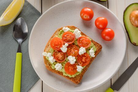 Toast with mashed avocado, cherry tomato and ricotta. Beautiful and delicious snack on white plate.