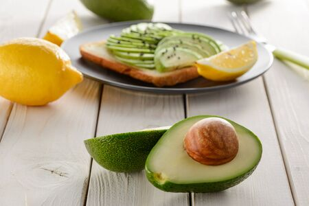 Avocado halves and toast with its slices on wooden table