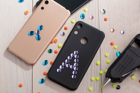 Attaching acrylic rhinestones onto phone cases with a glue gun. Top view on wooden table with craft materials. Stok Fotoğraf