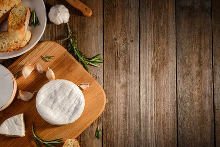 Camembert cheese, garlic, bread and rosemary on a rustic wooden table