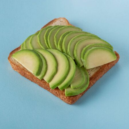 Toast with sliced avocado on blue background, closeup shot. Homemade vegan snack. Healthy food alternative for lunch. Banque d'images - 138555106