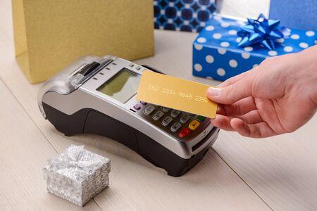 Cliente que paga por regalos de lujo con una tarjeta de crédito dorada. Pagos sin contacto y festivos.