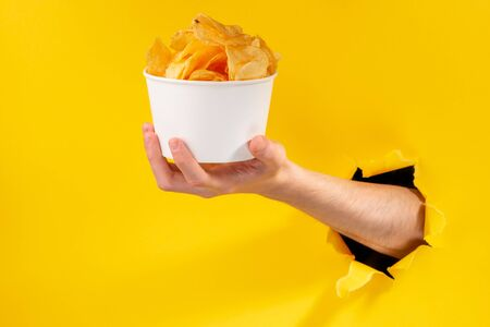 Hand giving a cup of potato chips through a torn hole in yellow paper background. Delicious crispy snack advertisement.
