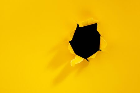 Torn hole in yellow paper background.