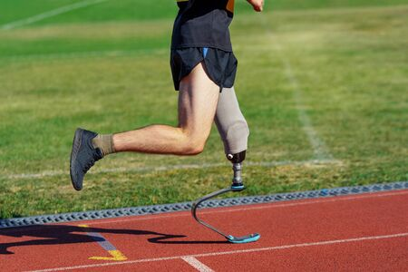 Amputee athlete participates in a race. Man with prosthetic leg running and aiming to win a competition.