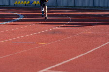 Stadion atleet met een handicap en hardlopen. Sportman met prothetisch been die een praktijk heeft.