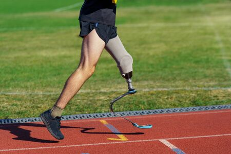 Parasportsman running on a stadium track. Amputee athlete with prosthetic leg participates in a race.
