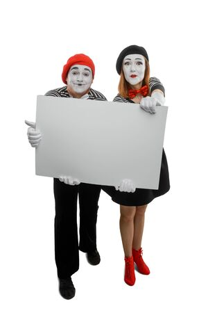 Smiling mimes showing big blank card for placing your content Banco de Imagens