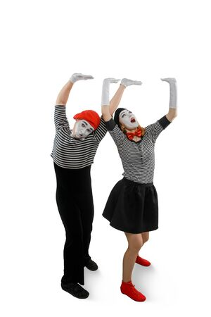 Two mimes posing on white background. Man and woman performing a pantomime Banco de Imagens