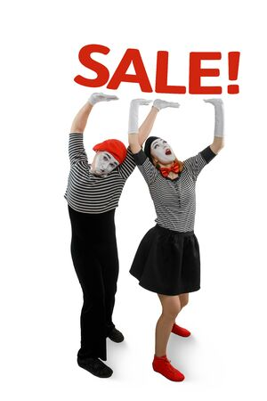 Two mimes posing on white background. Man and woman holding heavy lettering SALE