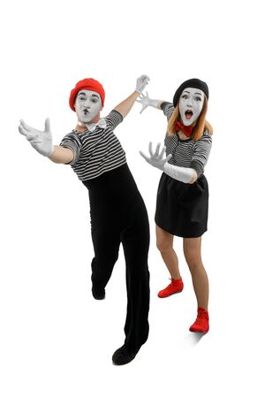 Two dancing mimes on white. Vertical studio shot of man and woman