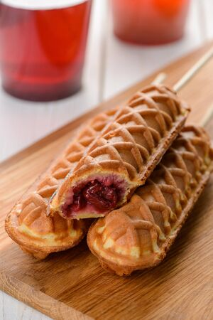 Pile of waffle cherry pops and two cups of tea. Delicious breakfast desserts for great mood. Tasty food still life.