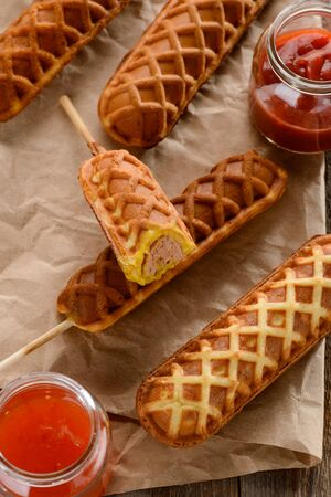 Waffle corn dogs on kraft wrapping paper. Served with ketchup and BBQ sauces. Trendy lunch meal.
