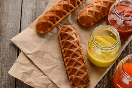 Amazing waffle corn dogs served with mustard, ketchup and BBQ sauces on kraft paper background. Lunch meal idea.