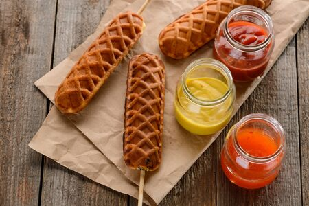 Corndogs, mustard, ketchup and barbecue. Delicious street food on wooden background.