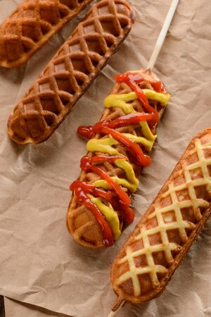 Waffle corn dogs with mustard and ketchup splashes. Appetizing skewer snacks with tasty sausage inside. Yummy! Stock fotó