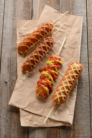 Waffle corn dogs on kraft wrapping paper. Skewer appetizers decorated with zigzag splashes of ketchup and mustard. Stock fotó - 140757443