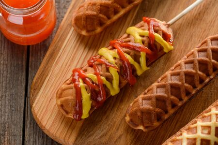 Appetizing corn dogs covered with ketchup and mustard. Deep-fried snacks on wooden cutting board.