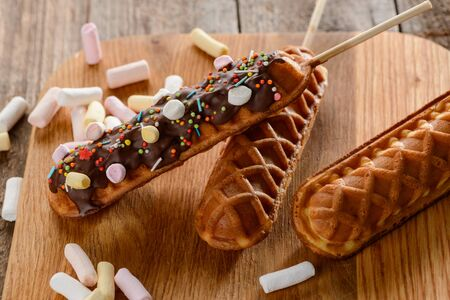 Close-up on waffle lollies. Wonderful desserts on a stick, being decorated with chocolate, marshmallow and sprinkles. Confectionery art. Stock fotó