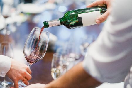 Waiter pouring red wine from a green bottle into a glass. Evening at a restaurant. Alcohol drinks, party and celebration.