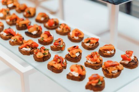 Rows of small delicious canapes on a tray. Gourmet food, perfect appetizers provided by catering company.