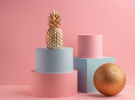 Golden pineapple, glitter ball, teal cube and pink round box on pink background. Minimalistic luxury design.