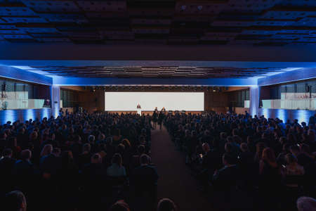 Conference hall full of audience and speakers on the stage