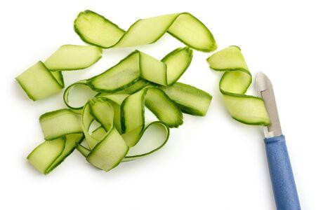 Peeler knife and cucumber shavings. Fresh vegetable cut into ribbons.
