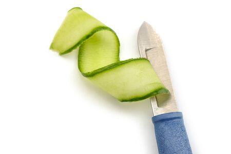 Peeler knife and cucumber shaving. Fresh vegetable cut into ribbon.