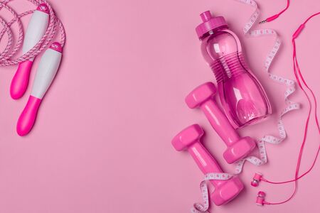 Fitness accesories, headphones and measure tape on pink background