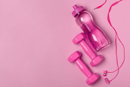 Dumbbells, bottle and headphones on pink background, flat lay with copy space. Sport and music accessories. Stock Photo