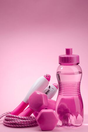 Water, dumbbells and a jump rope on pink background Stock Photo