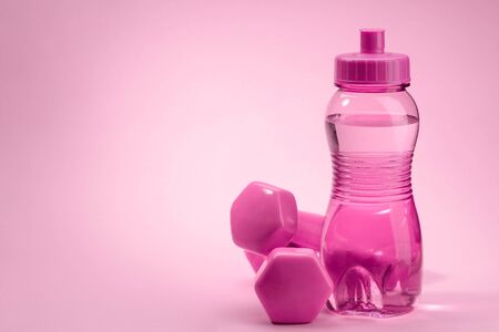 Bottle and dumbbells on pink background with copy space Stock fotó
