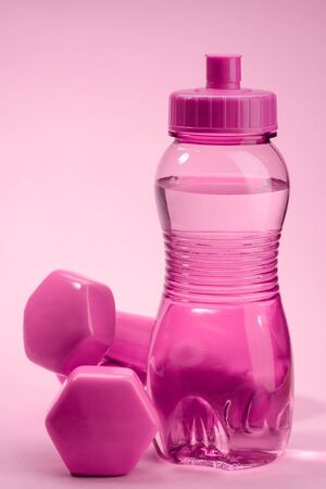 Pink bottle and dumbbellls. Gym accessory and equipment