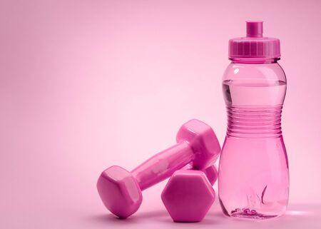 Bottle and dumbbells on pink background with copy space Stock Photo