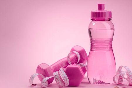 Dummbbells, bottle and measuring tape on pink background Stock fotó - 142418357