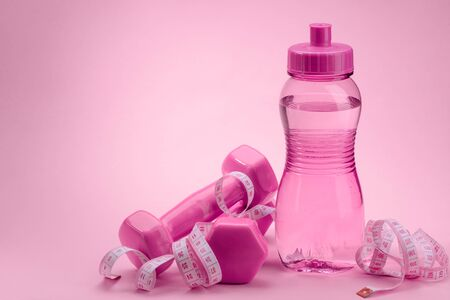 Dumbbels, measuring tape and bottle of water on pink background Stock fotó - 142418358
