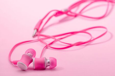 In-ear headphones on pink background, selective focus