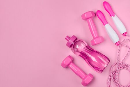Jump rope, bottle of water and dumbbells on pink background