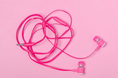 Top view on in-ear headphones on pink background