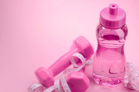 Dumbbels, measuring tape and bottle of water on pink background. Burn calories, weight loss and fitness.