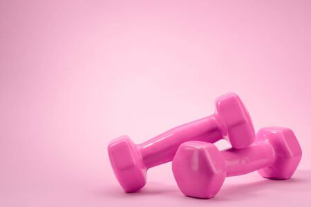 Dumbbells on pink background with copy space