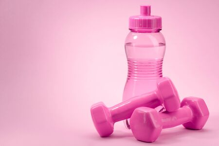 Pink bottle and dumbbellls on pink background with copy space Stock fotó - 142321091