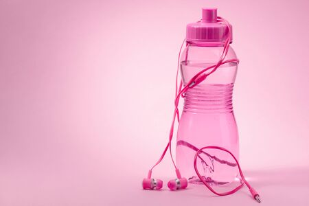 Headphones and bottle of water on pink background